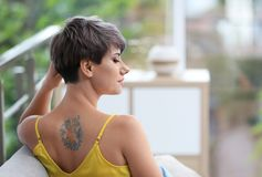 Trendy young woman with tattoo on sofa royalty free stock image