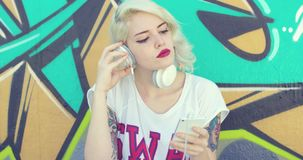 Trendy young woman with tattoos listening to music stock video