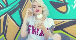 Trendy young woman with tattoos listening to music stock footage