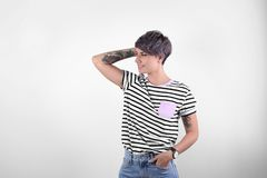 Trendy young woman with tattoos. On white background royalty free stock image