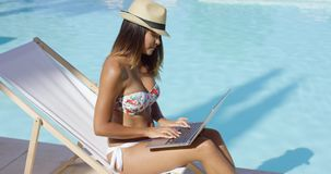 Trendy young woman using a laptop at the pool. As she relaxes on a deck chair in her bikini  sunglasses and trendy hat stock video
