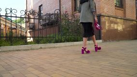 Trendy young woman walking at the street in slow motion. Elegant stylish woman in black dress and grey coat is walking at the urban street. Confident woman is stock video