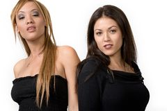 Trendy young women. Two trendy young women pose, standing shoulder to shoulder in black tops Stock Images