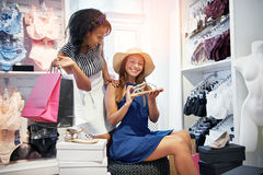 Trendy young women choosing a pair of shoes Stock Photos