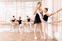 Trener baletniczych szkolnych pomocy młoda balerina wykonuje różnych chorograficznych ćwiczenia obraz royalty free