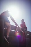 Trener pomaga dzieciaków wspinać się drewnianą ścianę podczas przeszkoda kursu szkolenia Obraz Stock