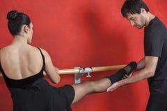 Trener Pomaga Żeńskiego Baletniczego tancerza Przy Barre W studiu Obraz Stock
