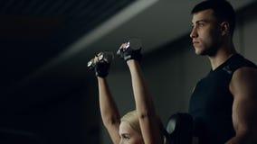 Trener pomaga kobiety ćwiczyć z dumbbells w sprawności fizycznej gym zdjęcie wideo