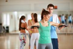 Trener pomaga kobiety podczas gdy ćwiczyć ręki w gym Fotografia Stock