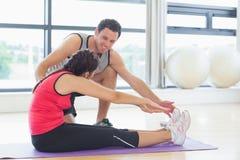 Trener pomaga kobiety z Pilate ćwiczy w sprawności fizycznej studiu Obrazy Royalty Free