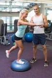 Trener pomaga kobiety z rozciąganiem ćwiczy przy gym Obrazy Royalty Free