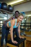 Trener pomaga kobiety z wunda krzesłem w sprawności fizycznej studiu obrazy stock