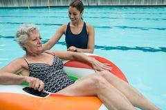 Trener pomaga starszej kobiety na nadmuchiwanym pierścionku zdjęcie royalty free