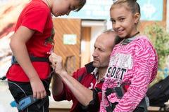 Trener robi zbawczemu czekowi nicielnica chłopiec przed wspinać się fotografia royalty free