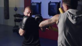 Trener trenuje boksera w gym, opracowywa, kopni?cie i obron?, zwolnione tempo zdjęcie wideo
