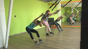 Trener uczy w gym ćwiczyć mężczyzny na zawiasach TRX podczas gdy wykonujący ćwiczenie twarzową estokadę zdjęcie wideo