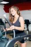 Trenes atléticos de la muchacha cardiios en el simulador de pasos Mujer en la sonrisa del gimnasio imágenes de archivo libres de regalías