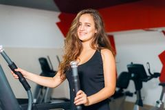 Trenes atléticos de la muchacha en el simulador de pasos Mujer en la sonrisa del gimnasio imagen de archivo