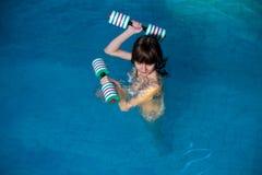 Trenes atractivos de la muchacha en aeróbicos de la aguamarina Foto de archivo libre de regalías