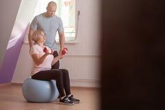 Trenes de mediana edad bonitos de la mujer con pesas de gimnasia imagen de archivo libre de regalías