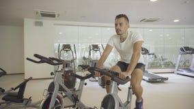 Trenes de trabajo duros del atleta en la bicicleta estática de giro metrajes