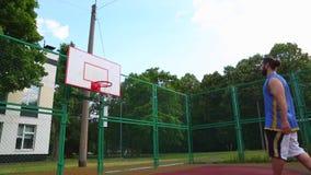 Trenes del jugador de básquet en la calle para anotar la bola en la cesta Juego de entrenamiento del baloncesto Deporte del conce metrajes