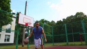 Trenes del jugador de básquet en la calle para anotar la bola en la cesta Juego de entrenamiento del baloncesto Deporte del conce almacen de metraje de vídeo