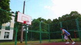 Trenes del jugador de básquet en la calle para anotar la bola en la cesta Juego de entrenamiento del baloncesto Deporte del conce almacen de video