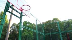 Trenes del jugador de básquet que juegan a baloncesto en el aire abierto Trenes de un hombre joven que saltan con un baloncesto p metrajes