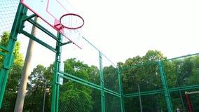 Trenes del jugador de básquet que juegan a baloncesto en el aire abierto Trenes de un hombre joven que saltan con un baloncesto p almacen de video