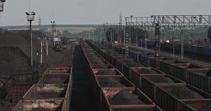 Trenes del panorama cargados con el carbón Coches ferroviarios en la estación con el mineral Carros en el cargamento de minerales almacen de video
