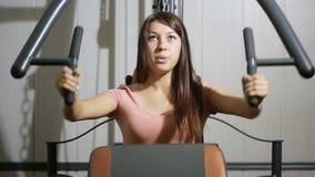 Trenes hermosos de la muchacha en el gimnasio mujer contratada a un simulador de los deportes almacen de video