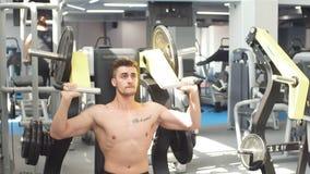 Trenes jovenes de un atleta en el gimnasio Culturista que bombea para arriba muscules del cuerpo superior almacen de metraje de vídeo