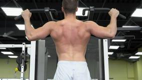 Trenes musculares jovenes del hombre en el gimnasio Atleta del entrenamiento del peso foto de archivo