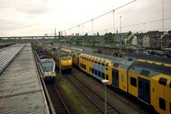 Trenes que pasan cerca de ciudad grande en Holanda fotos de archivo