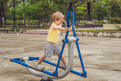 Treni del ragazzo di sport sull'istruttore trasversale ellittico immagini stock