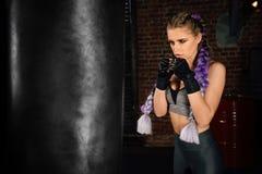 Treni della giovane donna in ring con il punching ball pesante Fotografia Stock