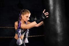 Treni della giovane donna in ring con il punching ball pesante Immagine Stock Libera da Diritti