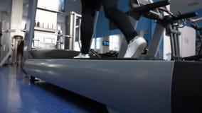 Treni della ragazza su una pedana mobile Camminando in ginnastica donna del club di forma fisica impegnata nella camminata Mette  video d archivio