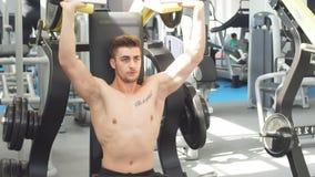 Treni giovani di un atleta nella palestra Culturista che pompa sui muscules dell'ente superiore video d archivio