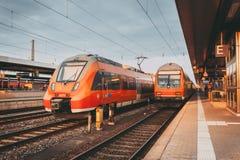Treni pendolari rossi ad alta velocità alla stazione ferroviaria Immagine Stock