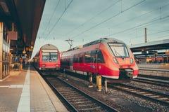 Treni pendolari rossi ad alta velocità alla stazione ferroviaria Fotografia Stock