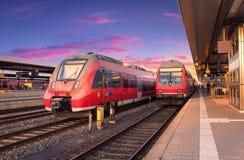 Treni pendolari rossi ad alta velocità sulla stazione ferroviaria Immagine Stock