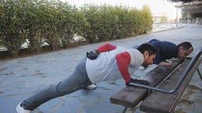 Trening z osobistym trenerem outdoors Dwa sprawności fizycznej mężczyzna robi jeden zbroił Ups opiera na ławce w parku jako część zbiory wideo