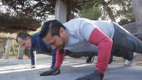 Trening z osobistym trenerem outdoors Dwa sprawności fizycznej mężczyzna robi klasczący Ups w parku jako część trening rutyny zdjęcie wideo