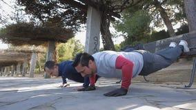 Trening z osobistym trenerem outdoors Dwa sprawności fizycznej mężczyzna robi Ups z ciekami wynoszącymi w parku jako część trenin zbiory wideo