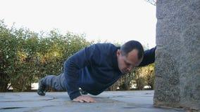 Trening z osobistym trenerem outdoors Męska atleta w wojskowego stylu inicjuje i spodnia robi podnoszącej ręce Ups w a zdjęcie wideo