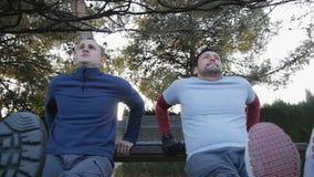 Trening z osobistym trenerem outdoors Niskiego kąta widok dwa sprawność fizyczna mężczyzna robi triceps ławce zamacza w parku jak zdjęcie wideo