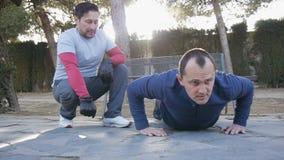 Trening z osobistym trenerem outdoors Sprawność fizyczna mężczyzna robi super wolnemu Ups w parku jako część trening rutyny zdjęcie wideo