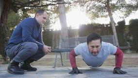 Trening z osobistym trenerem outdoors Sprawność fizyczna mężczyzna robi super wolnemu Ups w parku jako część trening rutyny zbiory